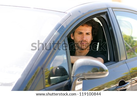 Portrait of a young man driving a car, looking in the rearview mirror - stock photo