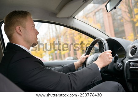 Portrait Of A Young Man Driving Car - stock photo