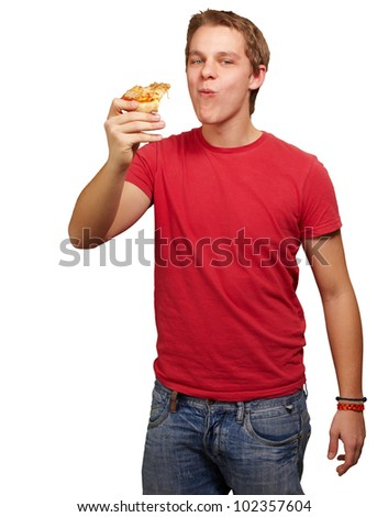 portrait of a young man eating a pizza portion over a white backgorund