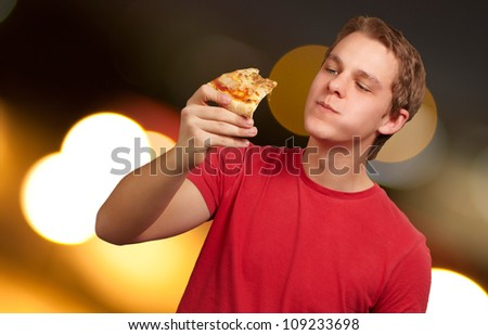 portrait of a young man eating pizza, background