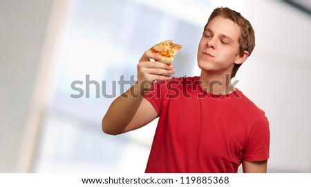 portrait of a young man eating pizza, background - stock photo
