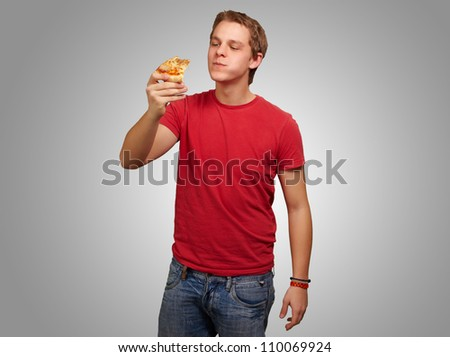 portrait of a young man eating pizza on a grey background