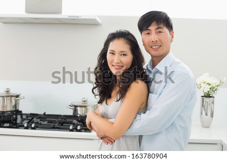 Portrait of a young man embracing woman from behind in the kitchen at home - stock photo