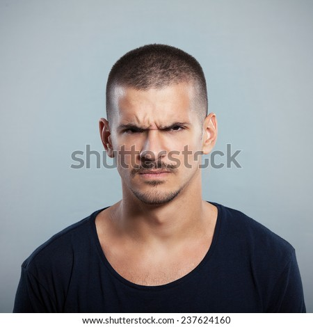 Portrait of a young man frowning. Studio shot. - stock photo