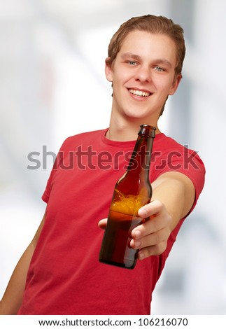 portrait of a young man holding a beer indoor - stock photo
