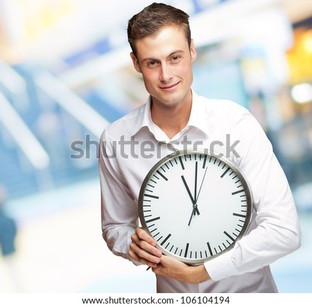 Portrait Of A Young Man Holding A Clock With His Hands - stock photo