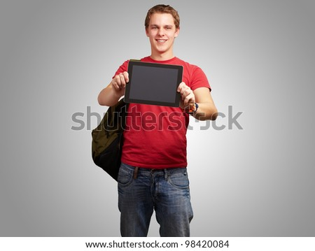 portrait of a young man holding a digital tablet over a grey background