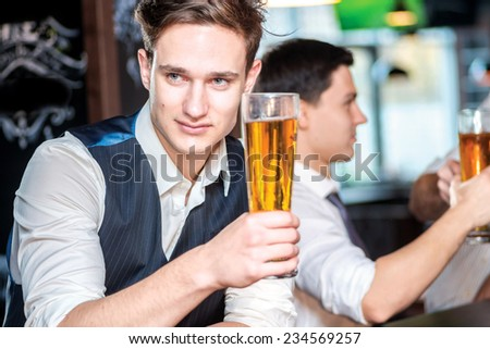 Portrait of a young man holding a glass of beer. Three cheerful friends met at the bar and drink a beer while the bartender is standing on the bar. Friends having fun together
