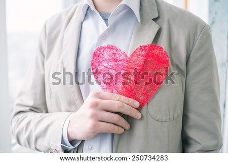 Portrait of a young man holding a heart