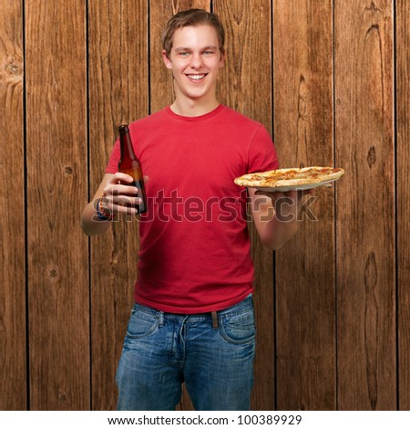 portrait of a young man holding a pizza and a beer against a wooden wall