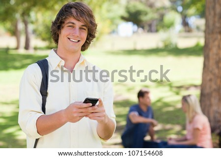 Portrait of a young man holding a smartphone in a park with friends in background - stock photo