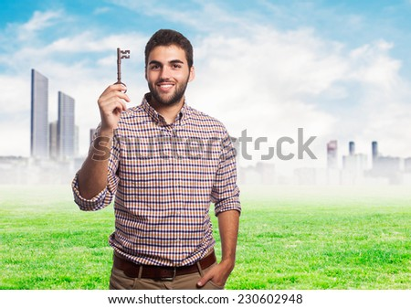 portrait of a young man holding an old key - stock photo
