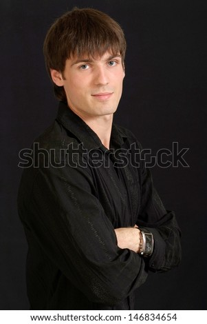 portrait of a young man in a black shirt on a black background