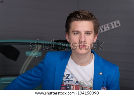 Portrait of a young man in a blue jacket in the car garage