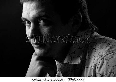 portrait of a young man in a shirt on a black background