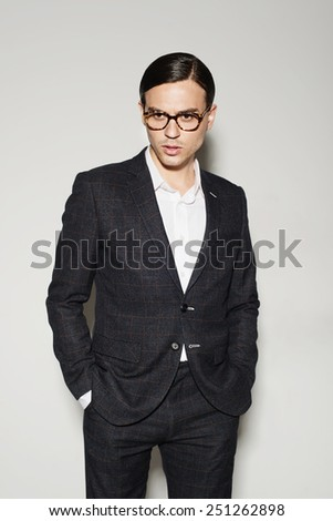 Portrait of a young man in studio on a white background in a suit and glasses with a thoughtful look - stock photo