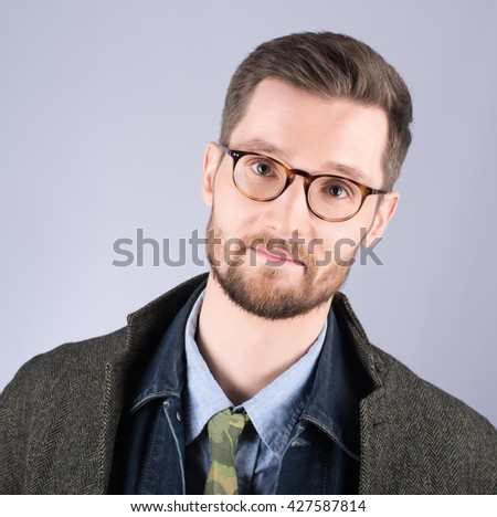 Portrait of a young man in stylish, modern clothes. Glasses and beard, a neutral grey background