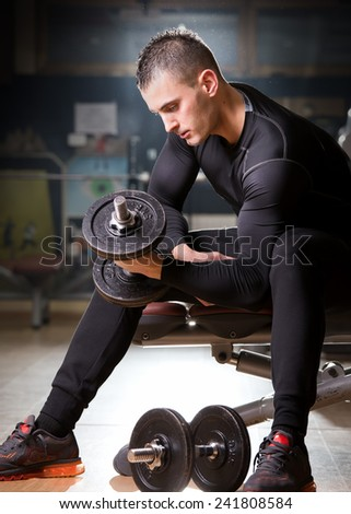 Portrait of a young man in the gym, exercise for the biceps. Lens flare - stock photo
