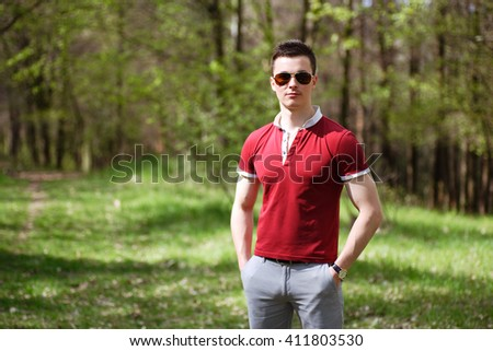 portrait of a young man in the park in sunglasses
