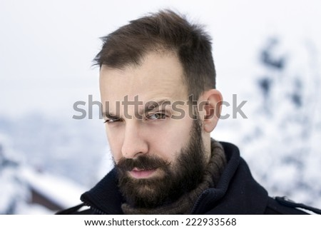 Portrait of a young man in the winter raising an eyebrow