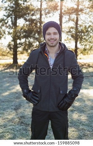 Portrait of a young man in warm clothing while having a walk in forest on a winter day - stock photo