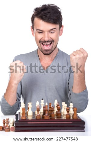 Portrait of a young man is celebrating victory in a game of chess. - stock photo