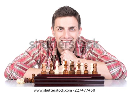 Portrait of a young man is playing a chess on a white background and looking at the camera. - stock photo