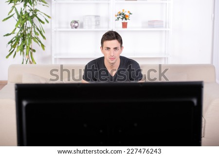 Portrait of a young man is watching television at home.
