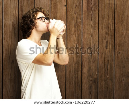 portrait of a young man kissing a piggy bank against a wooden wall