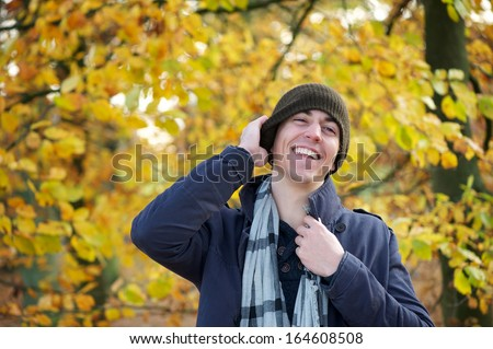 Portrait of a young man laughing outdoors on an autumn day - stock photo