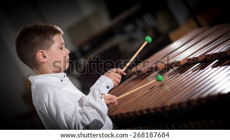 portrait of a young man learning to play the xylophone - stock photo