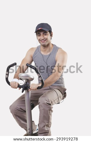 Portrait of a young man listening music while exercising over white background - stock photo