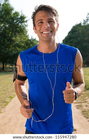Portrait Of A Young Man Listening To Music On Headphone While Jogging