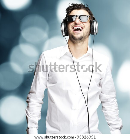 portrait of a young man listening to music with headphones against an abstract background