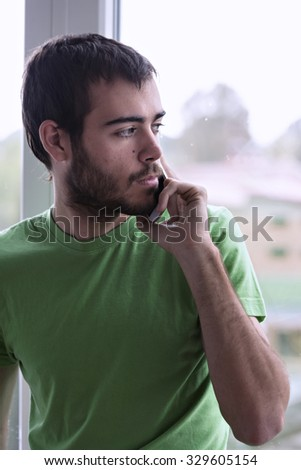 Portrait of a young man looking out the window and talking on the phone - stock photo