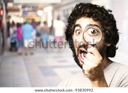 portrait of a young man looking through a magnifying glass against a crowded place