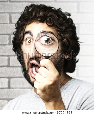 portrait of a young man looking through a magnifying glass against a grunge brick wall