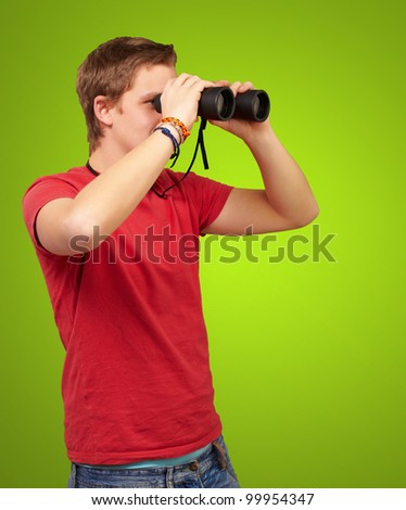 portrait of a young man looking through binoculars over a green background