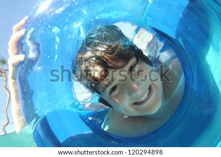 Portrait of a young man looking through inflatable ring in water