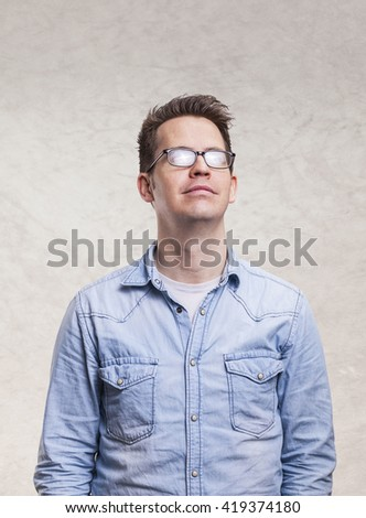 Portrait of a young man looking up -  isolated on light gray wall background - stock photo