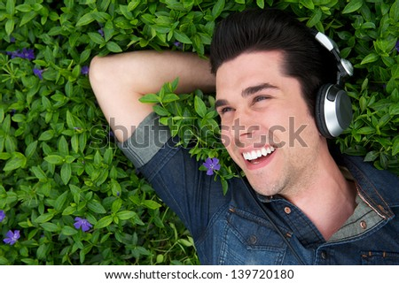 Portrait of a young man lying on grass smiling with headphones - stock photo
