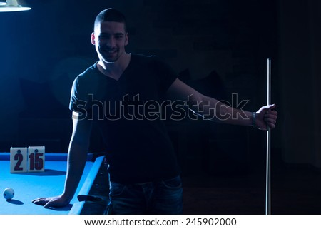 Portrait Of A Young Man Playing Billiards - stock photo