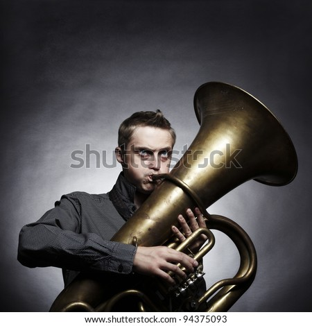 Portrait of a young man playing on the golden tuba