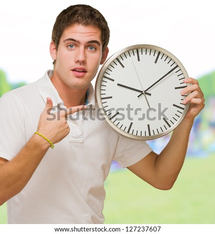 Portrait Of A Young Man Pointing at a Wall Clock at a park