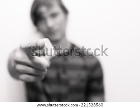 Portrait of a young man pointing with his finger - stock photo