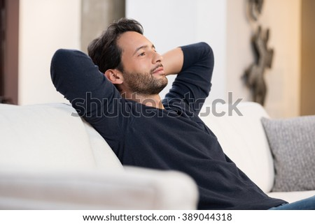 Portrait of a young man resting on sofa and thinking about the future. Handsome young man with hands behind head sitting on couch in living room. Positive man daydreaming and relaxing at home.  - stock photo