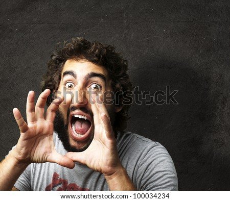 portrait of a young man screaming against a grunge wall - stock photo