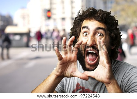 portrait of a young man screaming at a crowded city
