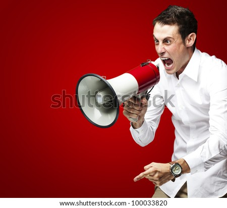 portrait of a young man screaming with a megaphone against a red background - stock photo