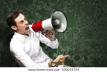 portrait of a young man screaming with a megaphone against a vintage wall - stock photo